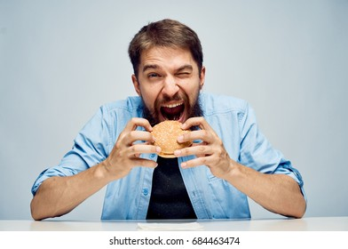 A man with a beard on a light background holds a hamburger, fast food.