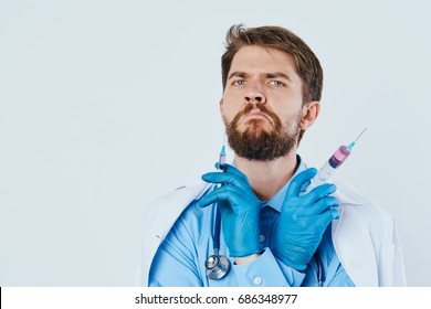 Man with a beard on a light background holds a syringe in a medical dressing gown, doctor, medicine.