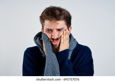 Man with a beard on a light background in a scarf, flu, sickness, sick.