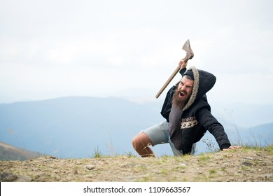Man with beard on shouting face conquers top of mountain with axe, sky background. Survive in wild nature concept. Hipster with axe surviving in mountains. Guy brutal and bearded in wild nature.