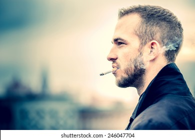 Man with beard on the top of the high building with cityscape on background