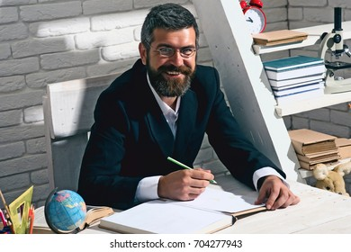 Man with beard on white brick wall background. Teacher and school supplies in classroom. Professor in glasses with happy face writes in book. Alternative education and knowledge concept.