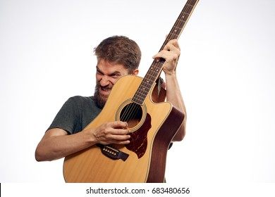A man with a beard on a white isolated background holds a guitar, music, musical instruments, play, strings.