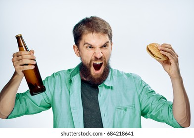 Man with a beard on a white isolated background holds a bottle of beer, alcohol.