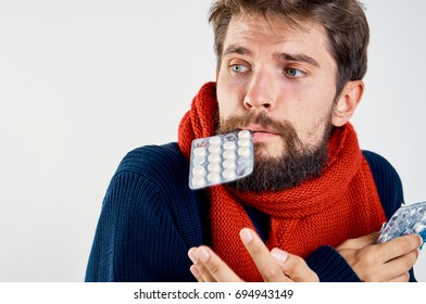Man with a beard on a white isolated background in a red scarf holds a pill in his mouth, illness, sick, flu.