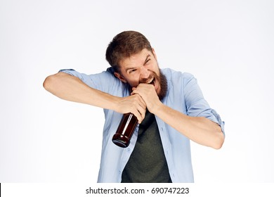 A man with a beard opens the bottle with his teeth against a light background