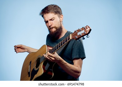 Man with a beard playing the guitar on a blue background, musical instruments.