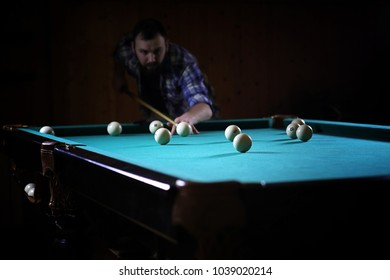 A man with a beard plays a big billiard. Party in 12-foot pool. Billiards in the club game for men. A man with a cue breaks the pyramid.