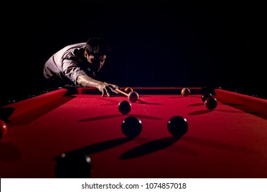 A man with a beard plays a big billiard.