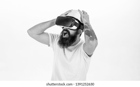 Man with beard in protective helmet isolated on white background. Construction worker with frightened look wearing VR gogglers. Bearded man scared of modelled cyber scene, 3D visualisation concept.