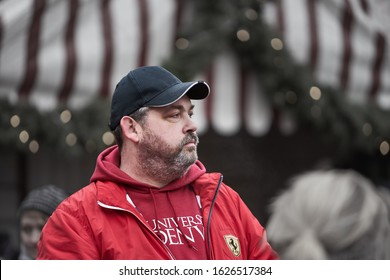 Man with beard in red hoody and black cap walking in old town 10-12-2019 Riga Latvia.