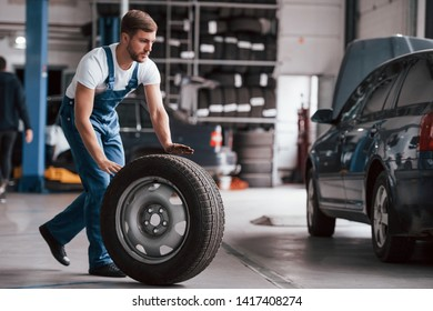 Man with beard rolls tire. Employee in the blue colored uniform works in the automobile salon.