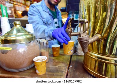 Man with beard selling Sahlep tea, traditional Turkish beverage is orchid, cinnamon, vanilla, hand's man in blue plastic globe pressing from big brass pot and pour in paper container grab glass