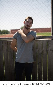 man with a beard and a short haircut walks in the stadium on a Sunny summer day. street style in clothes: skinny jeans and t-shirt. emotional portrait of a student. the old hockey rink and iron fence