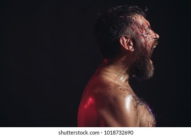 Man with beard shout with anger on black background. Bearded hipster with red blood on face and chest. Wizard, sorcerer, warlock. Magic, enchantment, witchcraft. Halloween holidays, copy space