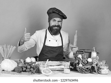 Man with beard sits by counter on green background. Cook with flirty face in burgundy uniform holds rolling pin showing thumbs up. Chef with pasta, vegetables and dough on table. Homemade food concept
