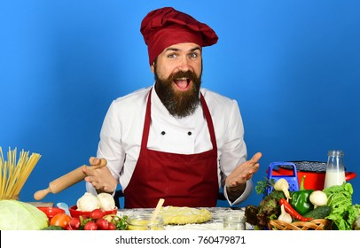 Man with beard sits by countertop on blue background. Homemade food concept. Chef with pasta, vegetables and dough on table. Cook with cheerful face in burgundy uniform holds rolling pin
