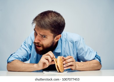 man with a beard sits at a table with a burger on a light background