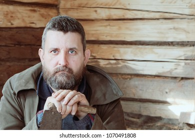 a man with a beard sits in a wooden log cabin, relying on a hand saw