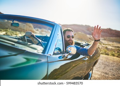 man with beard sitting in vintage car waving