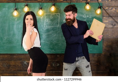 Man with beard slapping sexy student, chalkboard on background. Schoolmaster punishes sexy student with slapping on her buttocks. Girl on guilty and helpless face punished by teacher. Sex game concept