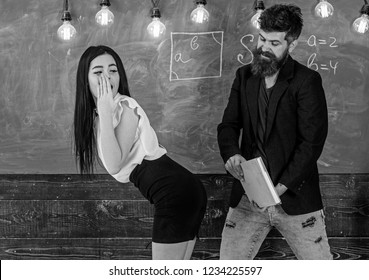 Man with beard slapping sexy student, chalkboard on background. Girl on guilty and helpless face punished by teacher. Schoolmaster punishes sexy student with slapping on her buttocks. Sex game concept