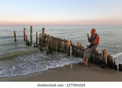 A man with a beard smokes on a ruined wooden pier on the beach
