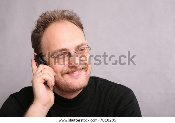 man with beard speaks on the cell phone