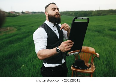 Man with a beard and sunglasses in the green field