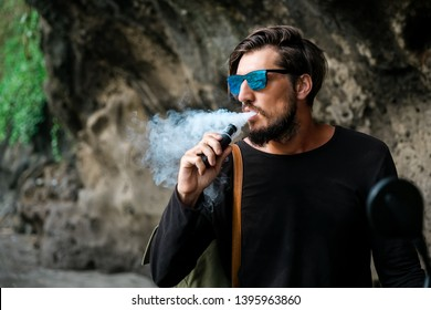 Man with beard and sunglasses seat on motorcycle smoking electronic sigarette outdoor on sunset beach. Young hipster male vaping on sea front.