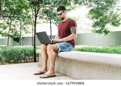 Man with a beard and sunglasses sitting on a bench in the middle of a park working remotely with his laptop
