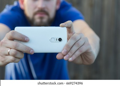 A man with a beard takes pictures on a smartphone