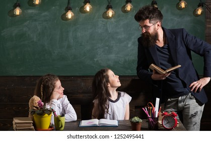 Man with beard teaches schoolgirls, reading book. Curious cheerful children listening teacher with attention. Teacher and girls pupils in classroom, chalkboard on background. Primary school concept