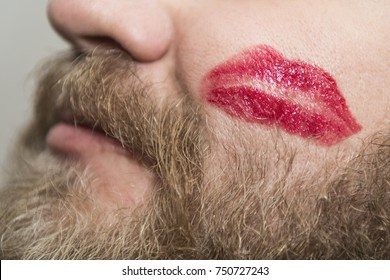 A man with beard that had some fun and got a kiss trace on the cheek. Close-up