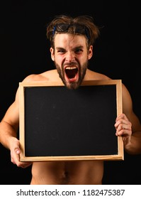 Man with beard and tousled hair black background. Man sexy muscular torso hold blackboard in front of his naked torso. Chalkboard advertisement copy space. Macho attractive nude guy hold blackboard.