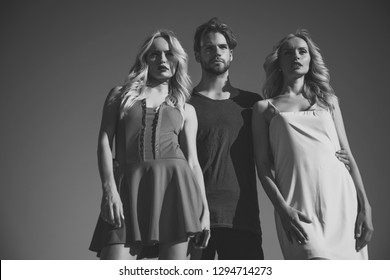 Man with beard with twins, relations. Love triangle and romance. Beauty and summer fashion. Family trust, polygamy, betrayal, swinger. Twins women with macho on blue sky background. friendship