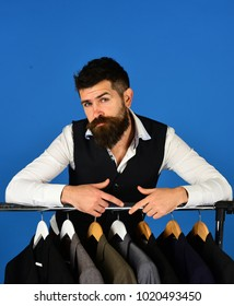 Man with beard in vest by clothes rack. Designer leans on clothes hangers with suits. Tailor with curious face near custom jackets on blue background. Tailoring and design concept.