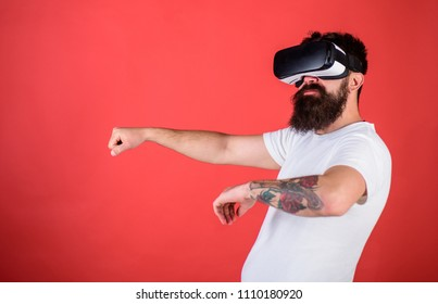 Man with beard in VR glasses driving car, red background. Virtual driving lessons concept. Hipster on confident face driving car in virtual reality with modern digital gadget.