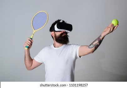 Man with beard in VR glasses, grey background. Hipster on concentrated face use modern technologies for sporty entertainment. VR tennis concept. Guy with VR glasses play tennis with racket and ball