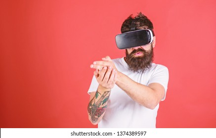 Man with beard in VR glasses shooting, red background. VR gadget concept. Guy with head mounted display shoot with gun in virtual reality. Hipster on busy face play in virtual reality.