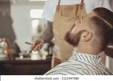 Man with a beard waits for a shave with a razor in a barbershop. Photo in vintage style