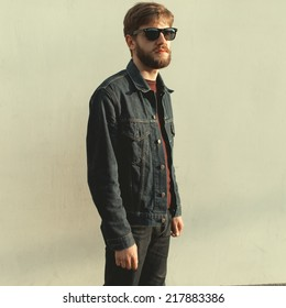 A man with a beard wearing glasses, a white wall in a sunny day