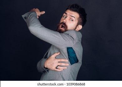 Man with beard wears jacket with hole on dark background. Bad quality of clothes concept. Surprised guy bought counterfeit or fake brand. Hipster chose small size jacket, seam torn under armpit.