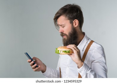 Man with beard in white shirt and suspenders eating junk food from a fast food hamburger or cheeseburger and talking on the phone on gray background