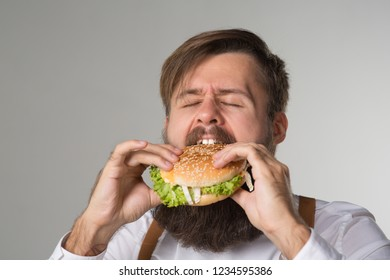 Man with beard in white shirt and suspenders eating junk food from a fast food hamburger or cheeseburger on gray background
