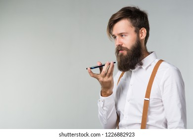 A man with a beard in a white shirt and yellow suspenders explains the idea on a smartphone on a gray background