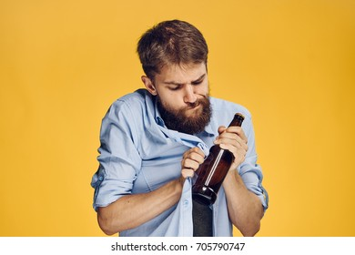 A man with a beard wipes a bottle of beer on a yellow background