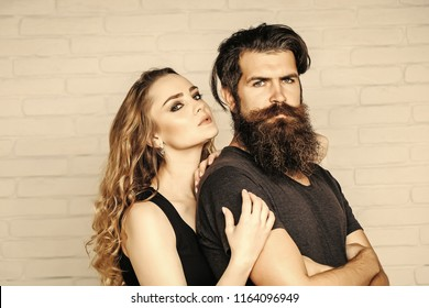 Man with beard and woman with long blond hair. Girl and bearded hipster. Couple in love hug on white brick wall. Hipsterism, subculture, trend. Fashion, beauty, style concept.