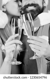 Man with beard and woman with smiles and kisses on background, defocused. Christmas time and love concept. Santa and sexy girl with drinks. Mister and Missis Claus hold glasses of champagne