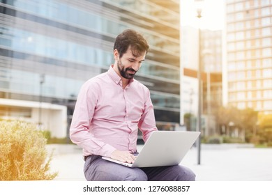 A man with beard working on laptop outside in business area